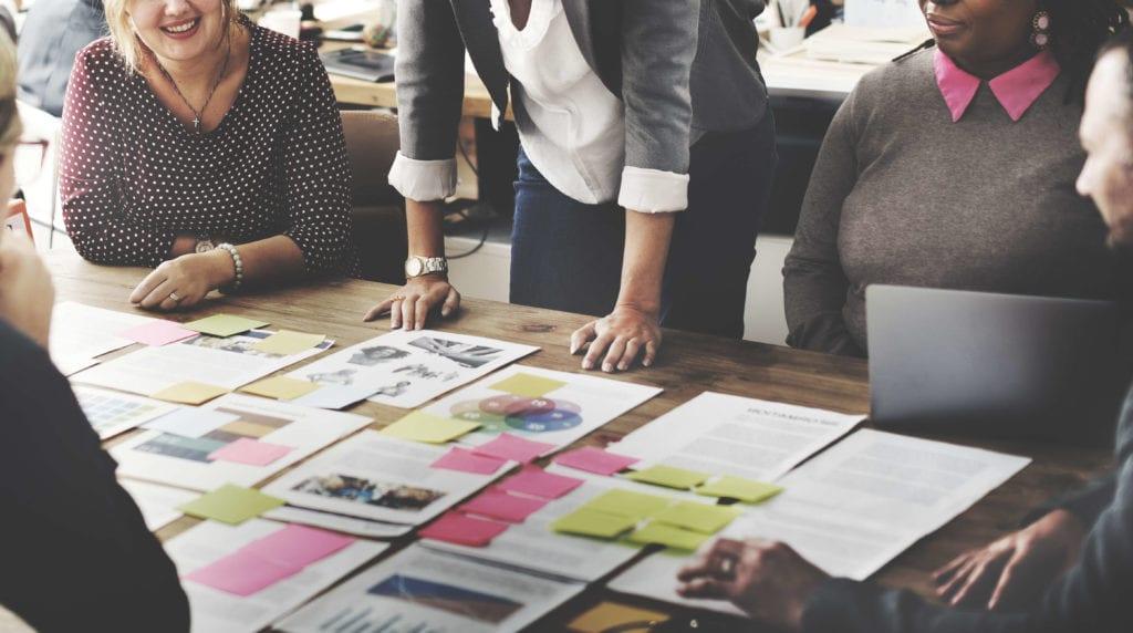 marketing team looking at flowchart on table